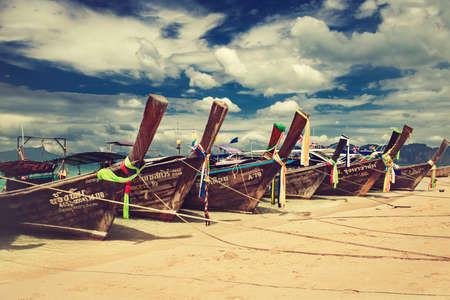 Thailand. Krabi province. Boats decorated by bright cloth  is moored in a turquoise lagoon of Phra Nang beach. Blue and cloudy sky on the background. Banco de Imagens - 78223822