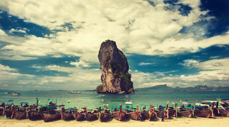 Thailand.Krabi province. Boats decorated by bright cloth  is moored in a turquoise lagoon of Phra Nang beach. Big not inhabited rock, blue and cloudy sky on the background.Panoramic view.