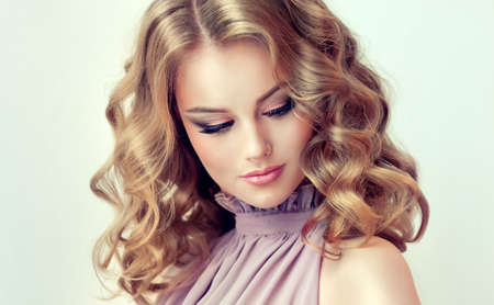 Attractive woman blonde with elegant hairstyle. Example of middle length,dense and curly hair.Gentle make up and long eyelashes. Banco de Imagens