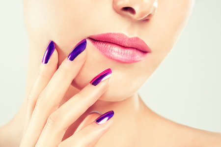 Pink lipstick on the lips and violet manicure on the nails. Close-up detail. Banco de Imagens