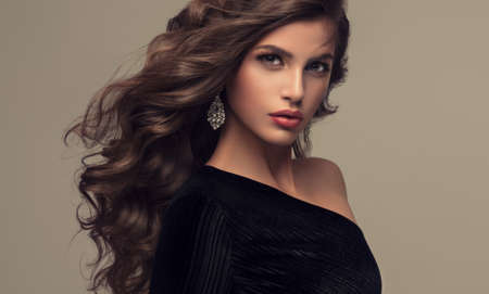Young woman brunette with voluminous, shiny and wavy hair . Beautiful model with long, dense and curly hairstyle. Frizzy hair.