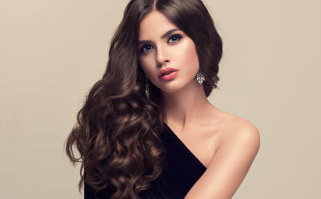 Young woman brunette with voluminous, shiny and wavy hair . Beautiful model with long, dense and curly hairstyle. Frizzy hair. Banco de Imagens - 79580138