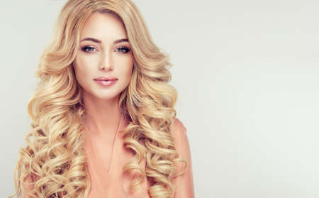 Close up portrait of attractive blonde woman with elegant and stylish hairstyle. Example of long,dense and curly hair. Archivio Fotografico