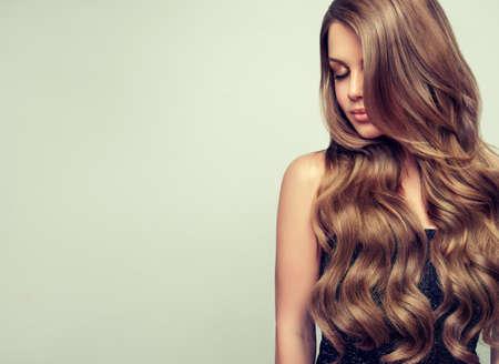 密なカール、手入れの髪で長い髪、魅力的なモデル。エレガントなメイクと完璧なヘアスタイルを持つ豪華な若い女性の肖像画。横道は一目します