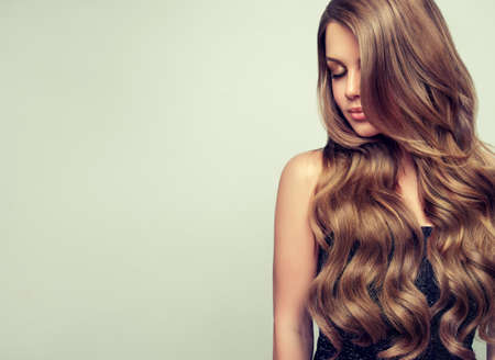 Langhaariges, ansprechendes Modell mit dichten, gewellten, gut gepflegten Haaren. Portrait von wunderschönen jungen Frau mit eleganten Make-up und perfekte Frisur. Seitenblick Standard-Bild - 80184605