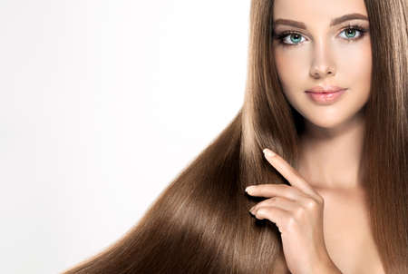 coloration: Young attractive girl-model with gorgeous, shiny, long, straight,brown hair. Good and healthy hair as resalt of right care.