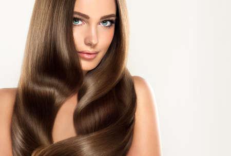 Modelo atractivo joven de la muchacha con el pelo magnífico, brillante, largo, derecho, marrón. Pelo bueno y saludable como resalt del cuidado derecho.