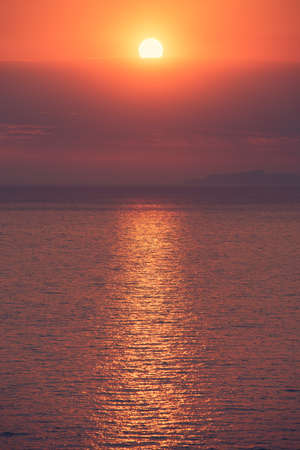 Vivid disk of the sun above tranquil sea. Sun road on the surface of the water. Idyllic atmosphere of tropical sunset..