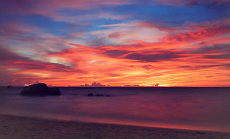 Tropical sunset. Last rays of sun, coloring the clouds in deep blue sky, in bright red shades. Idyllic atmosphere of tropical twilight.