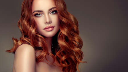 Young red haired woman  with voluminous, shiny and wavy hair . Beautiful model with long, dense and curly hairstyle. Tender look. Banco de Imagens