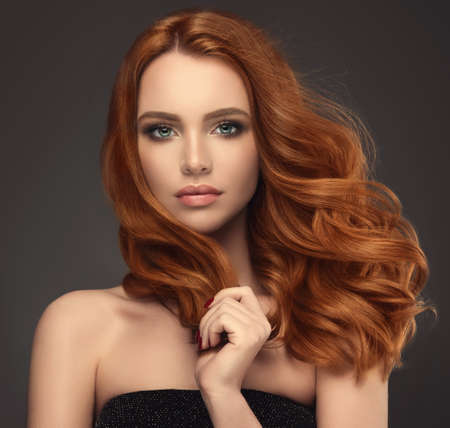 Young red haired woman  with voluminous, shiny and wavy hair . Beautiful model with long, dense and curly hairstyle. Flying hair. Banco de Imagens - 85255623
