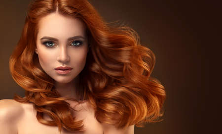 Young red haired woman  with voluminous, shiny and wavy hair . Beautiful model with long, dense and curly hairstyle. Flying hair. Banco de Imagens - 85255757
