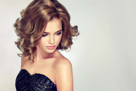 Beautiful model brunette with middle length curled hair and bright make up. Glamour evening hairdress. Short wavy hairstyle.