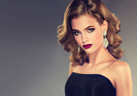Beautiful model brunette with middle length curled hair and bright make up, dressed in big jewelry earrings. Glamour evening hairdress. Short wavy hairstyle and tender look. Banco de Imagens