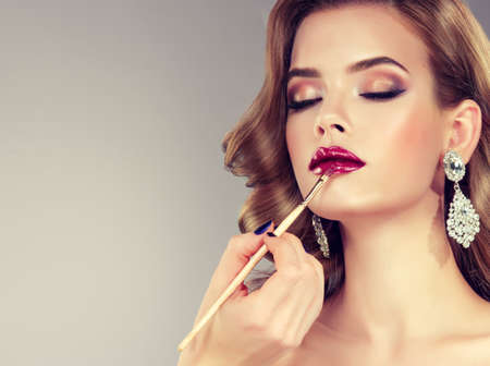 Hand of make-up master is painting lips of young beautiful model. Make-up in progress.Brunette with middle length curled hair and bright make up, dressed in big jewelry earrings.