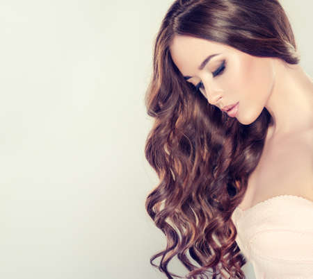 Young brown haired woman with voluminous, wavy hair soft tender skin. Beautiful model with long, and curly hairstyle. Loose hairstyle and evening make up. Banco de Imagens - 87919429
