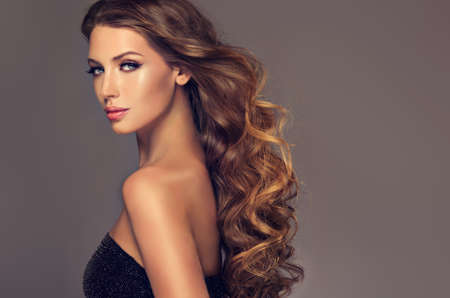 Young brown haired woman  with voluminous, shiny and wavy hair . Beautiful model with long, dense and curly hairstyle. Frizzy hair. Banco de Imagens - 87689936