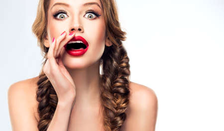 Lovely young woman is sharing fresh news with you. Brand-new gossips and rumors. Bright make up, red lipstick and manicure. Braided in a pigtails hairstyle. Banco de Imagens - 87689938