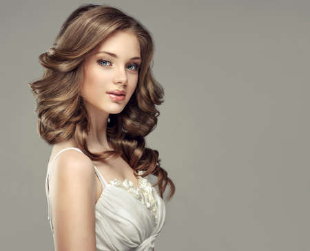 Sincere and tender look of young and gorgeous woman.Beautiful model with long, dense and curly hairstyle dressed in wedding or evening gown.Brunette with voluminous, shiny and curly hairstyle. Imagens
