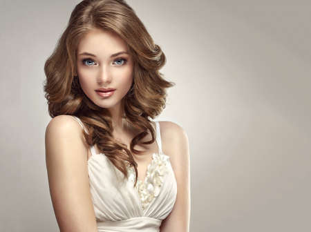 Sincere and tender look of young and gorgeous woman.Beautiful model with long, dense and curly hairstyle dressed in wedding or evening gown.Brunette with voluminous, shiny and curly hairstyle. Banco de Imagens - 90070024