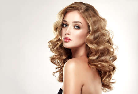 Woman blonde with voluminous, shiny,curly and loose hairstyle.. Beautiful model with long, dense and curly hairstyle. Frizzy and flowing hair.