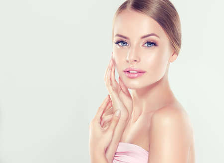 Young  blond-haired woman with clean fresh skin and soft, delicate make up. Cosmetology, plastic surgery,facial treatment and beauty technologies. Banco de Imagens - 90070026