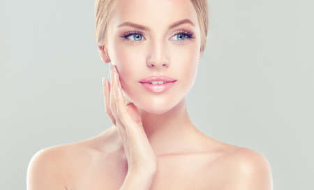 Woman  is touching tenderly to own face. Image of freshness and cleanliness.Cosmetology, plastic surgery,facial treatment and beauty technologies. Banco de Imagens - 90070029