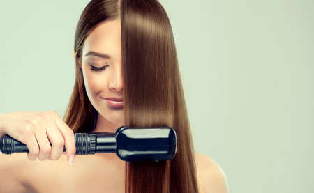 Young brown-haired attractive woman is demonstrating process of  hair straightening. Hair care, and beauty treatment.  Hair straightening by means of special equipment. Banco de Imagens - 95363225