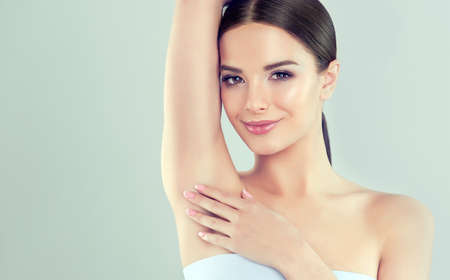 Young  brown-haired woman with clean fresh skin and soft, delicate make up. Woman  is touching own armpit tenderly. Image of freshness and cleanliness.Cosmetology, hair removal, plastic surgery,facial treatment and beauty technologies.