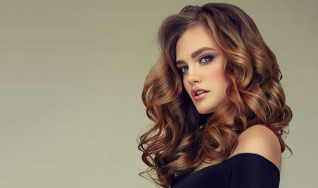 Young brown haired woman  with voluminous, shiny and wavy hair . Beautiful model with long, dense and curly hairstyle. Frizzy hair and  bright makeup. Banco de Imagens - 95887766