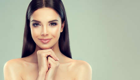 Young  brown-haired woman with clean fresh skin,soft, delicate make up and untied straight hairstyle is touching tenderly the face. Image of freshness and cleanliness.Cosmetology, plastic surgery,facial treatment and beauty technologies.