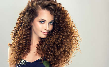 Gentle smile on the face of flawless young girl, vivid makeup and dense, curly hairstyle. Voluminous, spring-like,elastic curls in a hairstyle of young, pretty model.