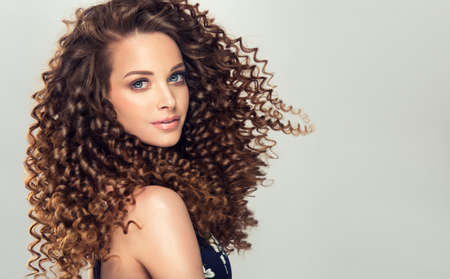 Dense, spring-like,elastic curls in a hairstyle of young, pretty model. Stylish hairdressing on the head and  trendy makeup on the face of perfectly looking woman.