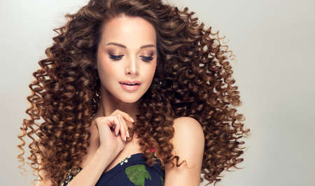 Stylish hairdressing on the head and  trendy makeup on the face of perfectly looking woman.  Gentle smile on the face of flawless young girl, vivid makeup and dense, curly hairstyle. Banco de Imagens - 103438710