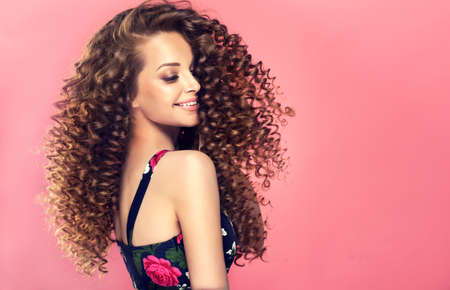 Young, wide smiling brown haired woman with voluminous hairstyle in profile. Dense, spring-like,elastic curls in a hairstyle of young, pretty model. Banco de Imagens - 103438711