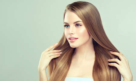 Young pretty model is touching own well groomed straight brown hair. Charming woman with clean fresh skin and soft, delicate make up.  Hairdressingand beauty technologies. 스톡 콘텐츠