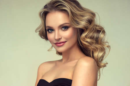 Hairdressing art and hair care.  Pretty blond-haired model with middle length curly, loose hairstyle and attractive makeup. Banco de Imagens - 104856663