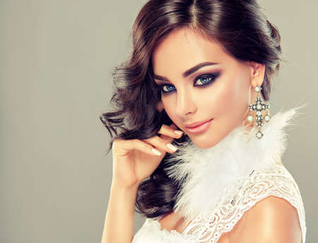Pretty, brown haired model in a bright middle east style makeup dressed in translucent evening gown. Elegant curly hairstyles and tender look. Banco de Imagens - 110779521