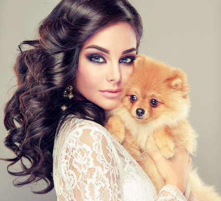 Portrait of young romantic woman with the small nice dog in hands.  Pretty, brown haired model in a bright oriental style makeup dressed in translucent evening gown. Banco de Imagens - 110779384