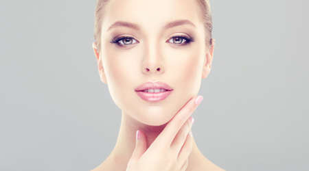 Young  beautyfull woman with clean fresh skin and soft, delicate make up. Woman  is touching own face tenderly. Image of freshness and cleanliness.Cosmetology. Banco de Imagens