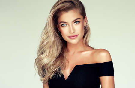 Young golden haired pretty model tenderly looking ot viewers with light smile. Portrait of gorgeous young woman with elegant make up and freely lying colored hairstyle.