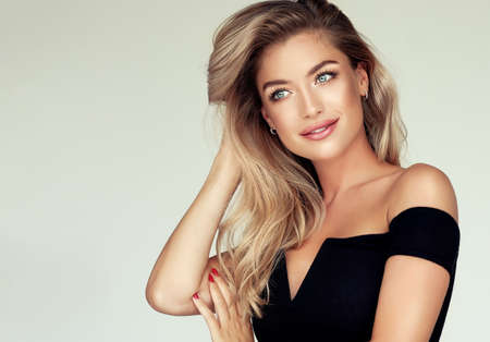 Young golden haired pretty model tenderly looking aside with light smile and touching  well groomed hair. Hair coloration, hair care and cosmetology.