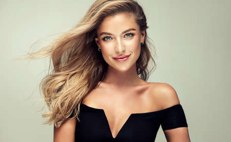 Young golden haired pretty model tenderly looking ot viewers. Portrait of gorgeous young woman with elegant make up and freely lying colored hairstyle. Hair coloration, hair care and cosmetology. Banco de Imagens