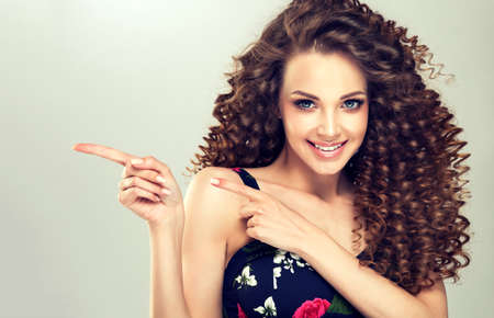 Young, wide smiling brown haired woman with voluminous hairstyle is pointing aside.Apparent gesture for advertisement. Brown haired woman with voluminous and curly hairstyle. Zdjęcie Seryjne