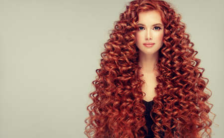 Portrait of young, attractive young model with incredible dense, long, curly red hair.Frizzy hair.
