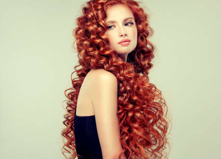 Pale skinned attractive young model with incredible dense, long, curly red hair. Pretty woman is demonstrating beauty and strength of natural hair. Thick, spring-like,elastic curls in a hairstyle.Hair care and hairdressing. Banco de Imagens - 113375040
