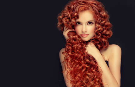 Pale skinned attractive young model with incredible dense, long, curly red hair. Pretty woman is demonstrating beauty and strength of natural hair.