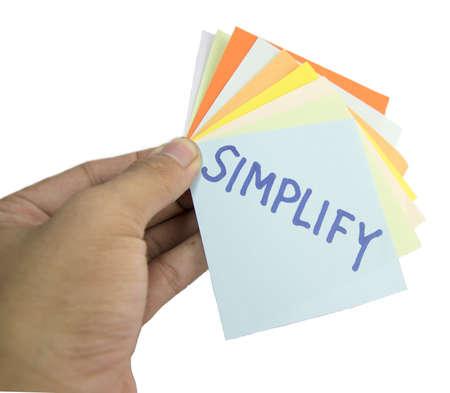 vereenvoudigen: motiverende slogan op een hand van kleurrijke herinnering notities op wit wordt geïsoleerd Stockfoto