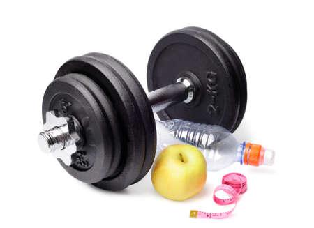 adjustable dumbbell: Dumbbells, apples, a bottle and centimeter isolated on white background