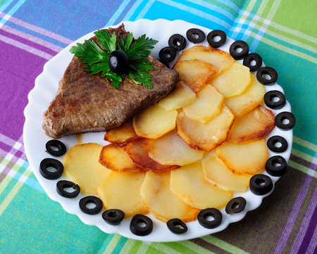 Veal with fried potatoes on a plate photo